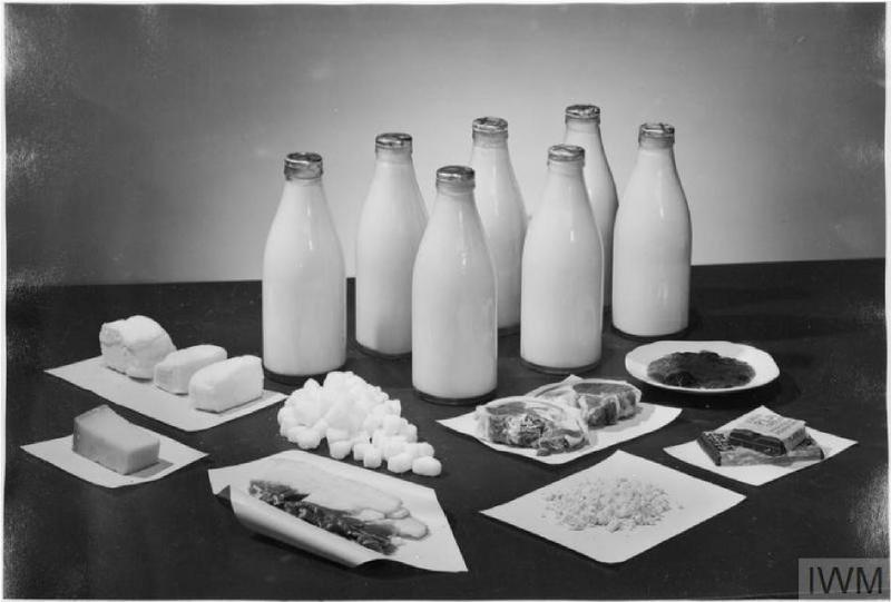 A photograph of weekly rations for two people, including seven pints of milk, two cuts of meat, a block of cheese, and other items