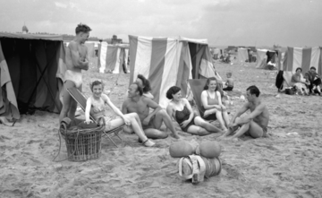 Young people sat around beach huts in 1950