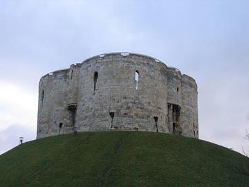 Photograph of Clifford's Tower in York. It is a 13th century stone tower, positioned on top of a Norman motte, which was probably used as a treasury and later as a prison.