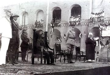 A photograph taken at the coronation of King Faisal of Iraq in 1921. Faisal sits in the centre, surrounded by officials and honorary guests.