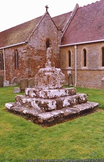 A photograph of a preaching cross outside a church. The cross is well-worn stone and sits on top of a square stone plinth, with three steps leading down from it on all four sides.